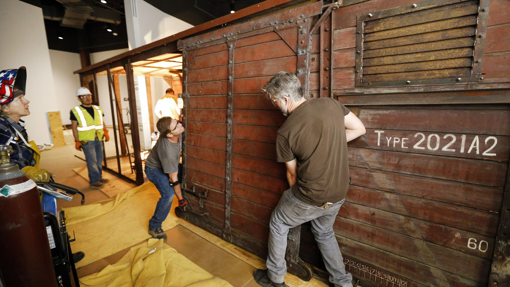 Jeff Green (right) and Dennis Manske begin installing a door on the rail car that'll be on display at the new Dallas Holocaust and Human Rights Museum when it opens in the West End in September.