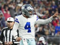 Dallas Cowboys quarterback Dak Prescott (celebrates after throwing a 1-yard touchdown  pass to wide receiver CeeDee Lamb during the third quarter of an NFL football game against the New England Patriots on Sunday, Oct. 17, 2021, in Foxborough, Mass.