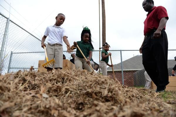 Second-grade students Jumoke Henry (left) and Jamyah Anderson raked leaves to be used for compost inside the teaching garden at the Meadows Elementary School.