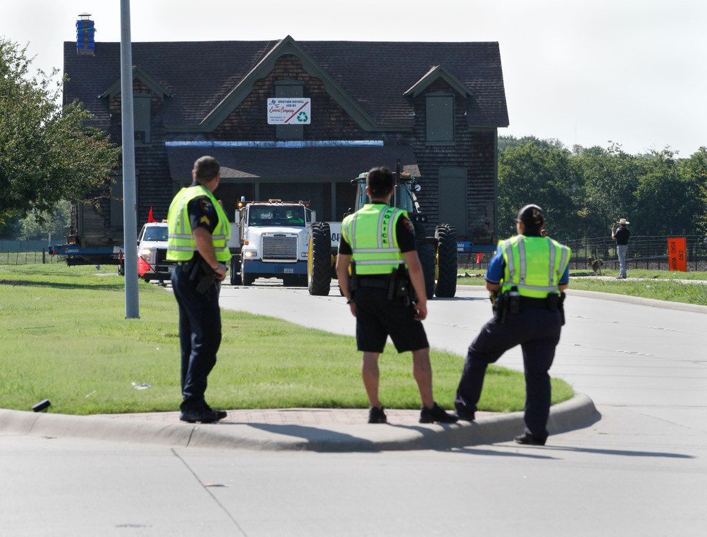 Three Plano police officers watch as the Collinwood Home, built around 1861, is moved westbound in the eastbound lanes of Spring Creek Parkway.
