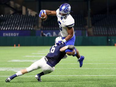 Fort Worth Nolan running back Emeka Megwa (6) leaps over Fort Worth All Saints cornerback Peyton Kramer (6) during the second half at Globe Life Park in Arlington, Saturday, December 5, 2020.