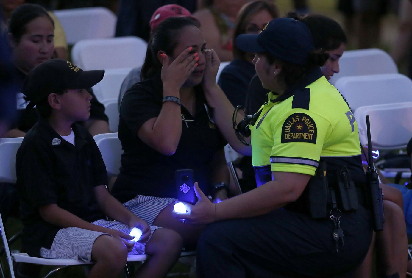 Kristy Zamarripa (center) wipes tears away as she's comforted by Dallas Bike Officer Ana Arrona (right) as Kristy's son Dylan Hoover looks on during the Tribute 7/7 closing ceremony at Dallas Police Memorial in Dallas, Friday, July 7, 2017. Her partner, Patrick Zamarripa, was one of the Dallas police officers killed.