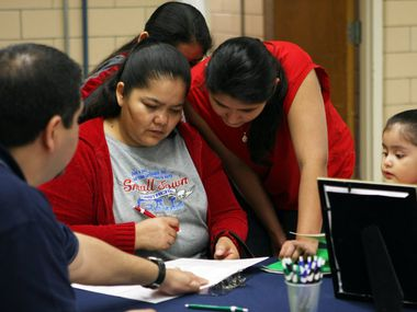 Maria Guerrero, right, with her children, listens to Aetna employee Louis Limas, left, as he explains Maria's health insurance options during a Arlington ISD and Texas Tarrant County CHIP Coalition helping Arlington parents qualify their children for the state's Children's Health Insurance Program on Jan. 23, 2010 at Webb Elementary in Arlington, Texas. Tarrant and Dallas counties are among the top counties with the most uninsured children, according to a 2019 report. (Ben Torres/Special Contributor)