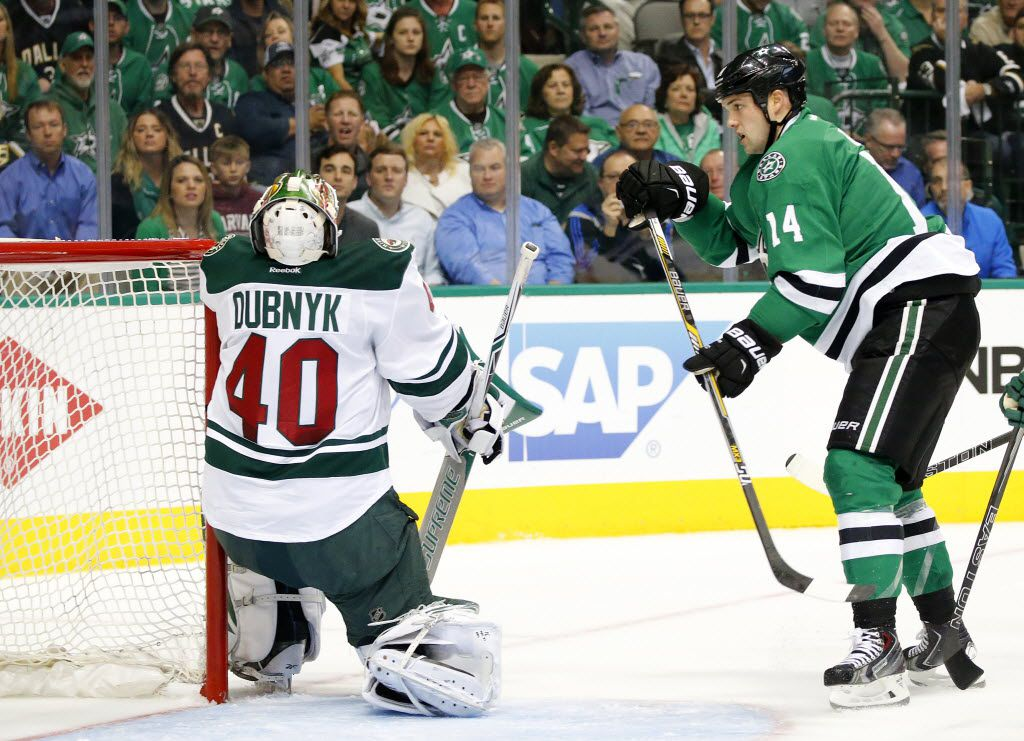 Minnesota Wild goalie Devan Dubnyk (40) takes a shot to the face mask as Dallas Stars left wing Jamie Benn (14) closes in the net in the first period of the Game 1 playoff 2at the American Airlines Center in Dallas,Thursday, April 14, 2016. (Tom Fox/The Dallas Morning News)