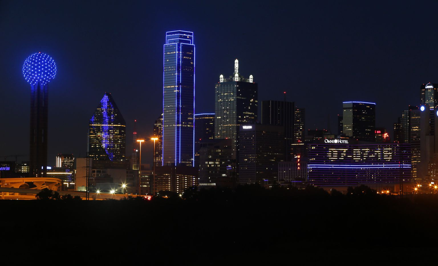 """The Omni Dallas Hotel (right) reads """"07-07-16"""" as the skyline of Dallas is aglow in blue."""