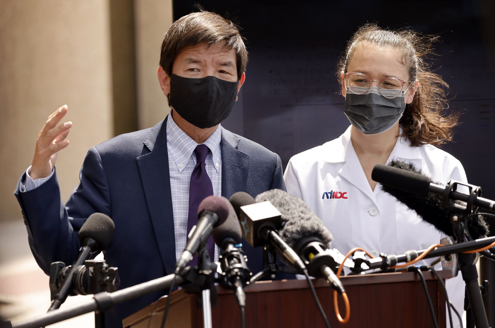 Dallas County Health and Human Services Director Dr. Philip Huang (left) and Dr. Emma Dishner of the North Texas Infectious Disease Consultants answered questions from the media about the current state of the coronavirus delta variant outside the county health building in Dallas on Tuesday. (Tom Fox/The Dallas Morning News)