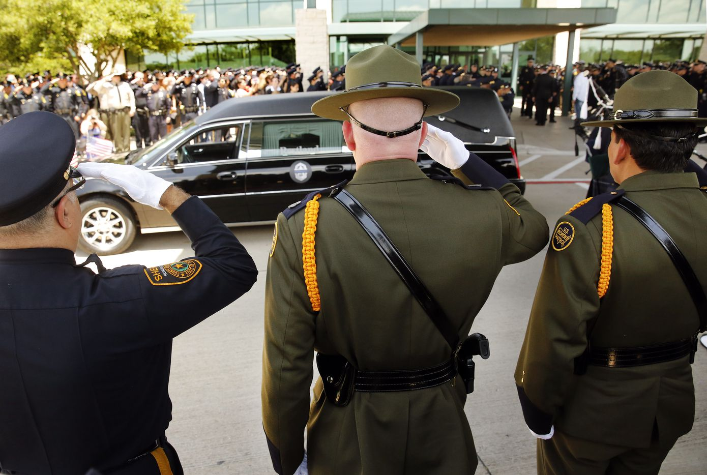 Border Patrol officers (right) and others salute as the casket of fallen Dallas police officer Lorne Ahrens is brought out of Prestonwood Baptist Church in Plano, Wednesday, July 12, 2016.