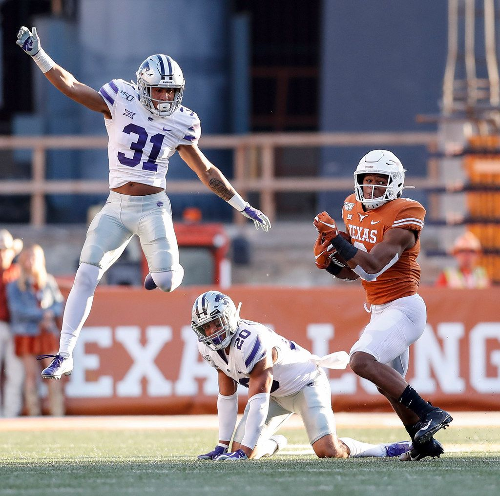 AUSTIN, TX - NOVEMBER 09:  Roschon Johnson #2 of the Texas Longhorns runs the ball after avoiding a tackle by Denzel Goolsby #20 of the Kansas State Wildcats and Jahron McPherson #31 in the third quarter at Darrell K Royal-Texas Memorial Stadium on November 9, 2019 in Austin, Texas.  (Photo by Tim Warner/Getty Images)