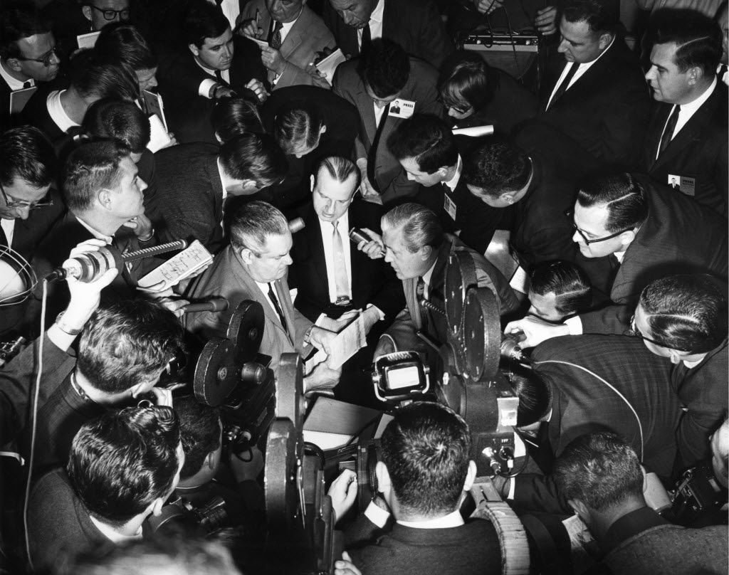 Jack Ruby is surrounded by members of the media during a recess in his trial.  His defense attorneys, Joe Tonahill (left) and Melvin Belli (right) sit with him.