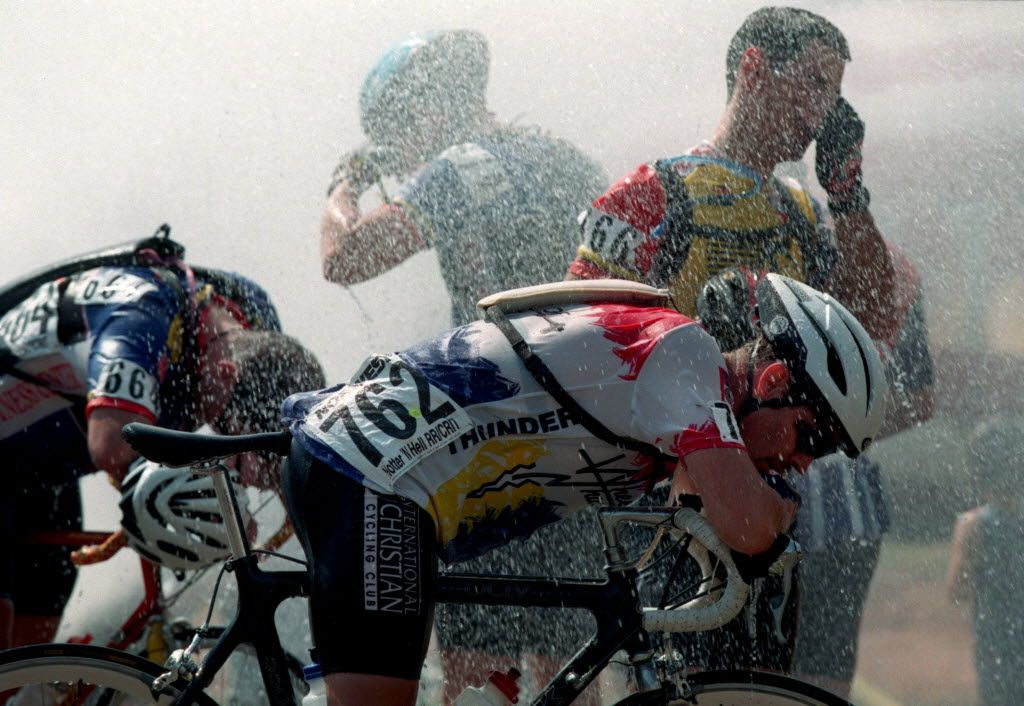 Exhausted cyclists cool  down  under the spray of a water hydrant after  completing the Hotter 'N Hell Hundred race