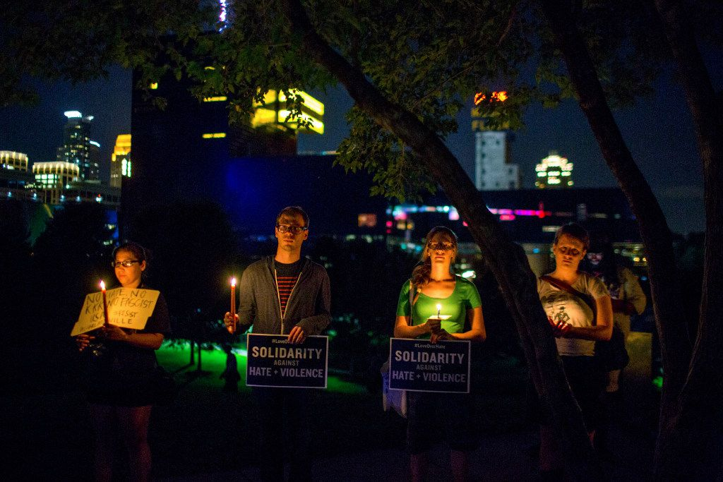 People stand atop a hill for a candlelight vigil in solidarity with Charlottesville, Virginia, counter-protesters at Gold Medal Park in Minneapolis on Saturday night, Aug. 12, 2017. (Courtney Pedroza/Star Tribune via AP)
