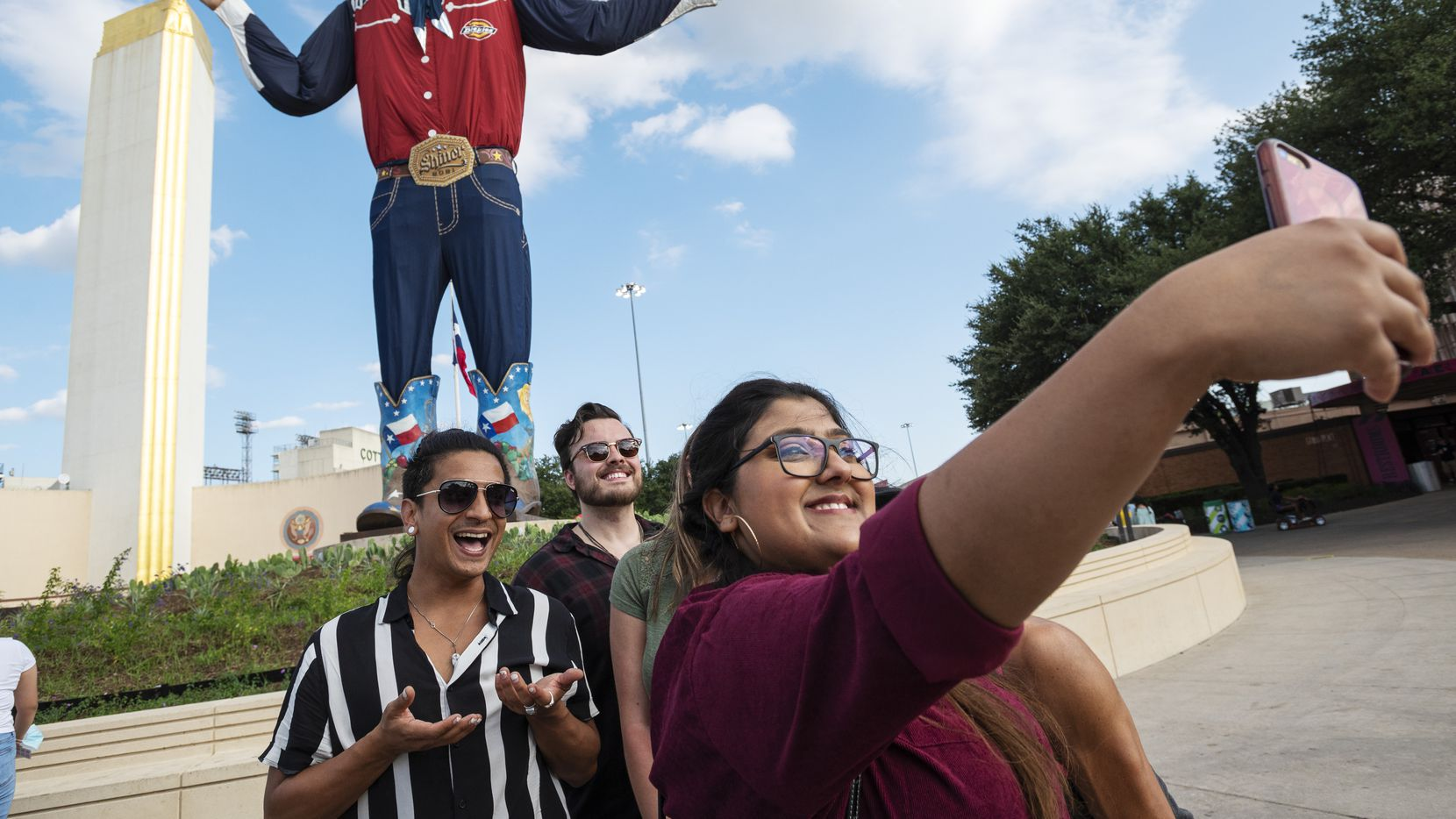 Nehan Farhat, 24, takes a selfie with a group of friends including Carlos Valdez, 34, left, and Dylan Bartlett, 27, center, as they celebrated her first time at the State Fair of Texas, on Sept. 29, 2021 at Fair Park in Dallas.