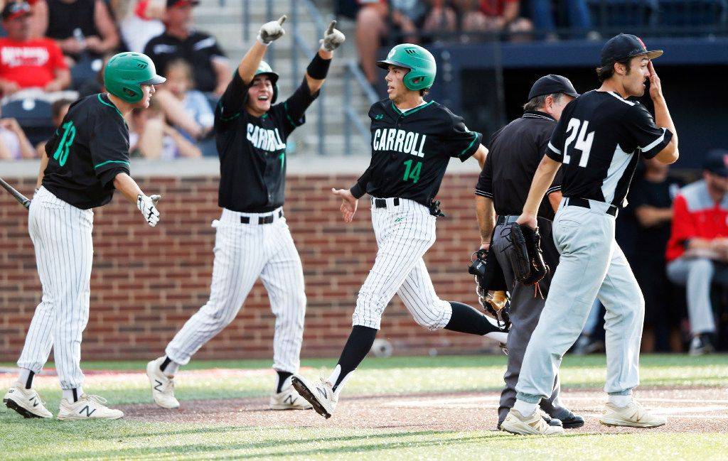 Southlake Carroll's Adam Stephenson (14) celebrates with Kole Ramage (13) after scoring a run as Arlington Martin's Austin Bain (24) watches in the fifth inning of play in game 1 of the best-of-3 Class 6A Region I final playoff at Dallas Baptist University in Dallas Thursday, June 1, 2017. Southlake Carroll won the first game 5-0. (Vernon Bryant/The Dallas Morning News)