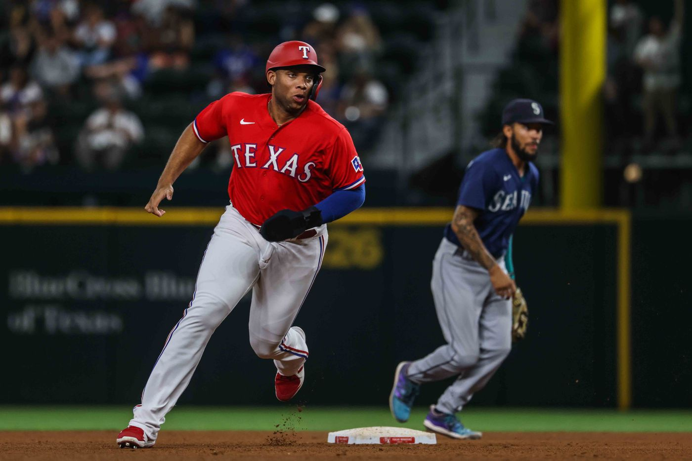 Texas Rangers Curtis Terris (83) runs to third base after Jason Martin (50) makes a hit against Seattle Mariners during  fourth inning at Globe Life Field in Arlington, Texas, Friday, July 30, 2021. (Lola Gomez/The Dallas Morning News)
