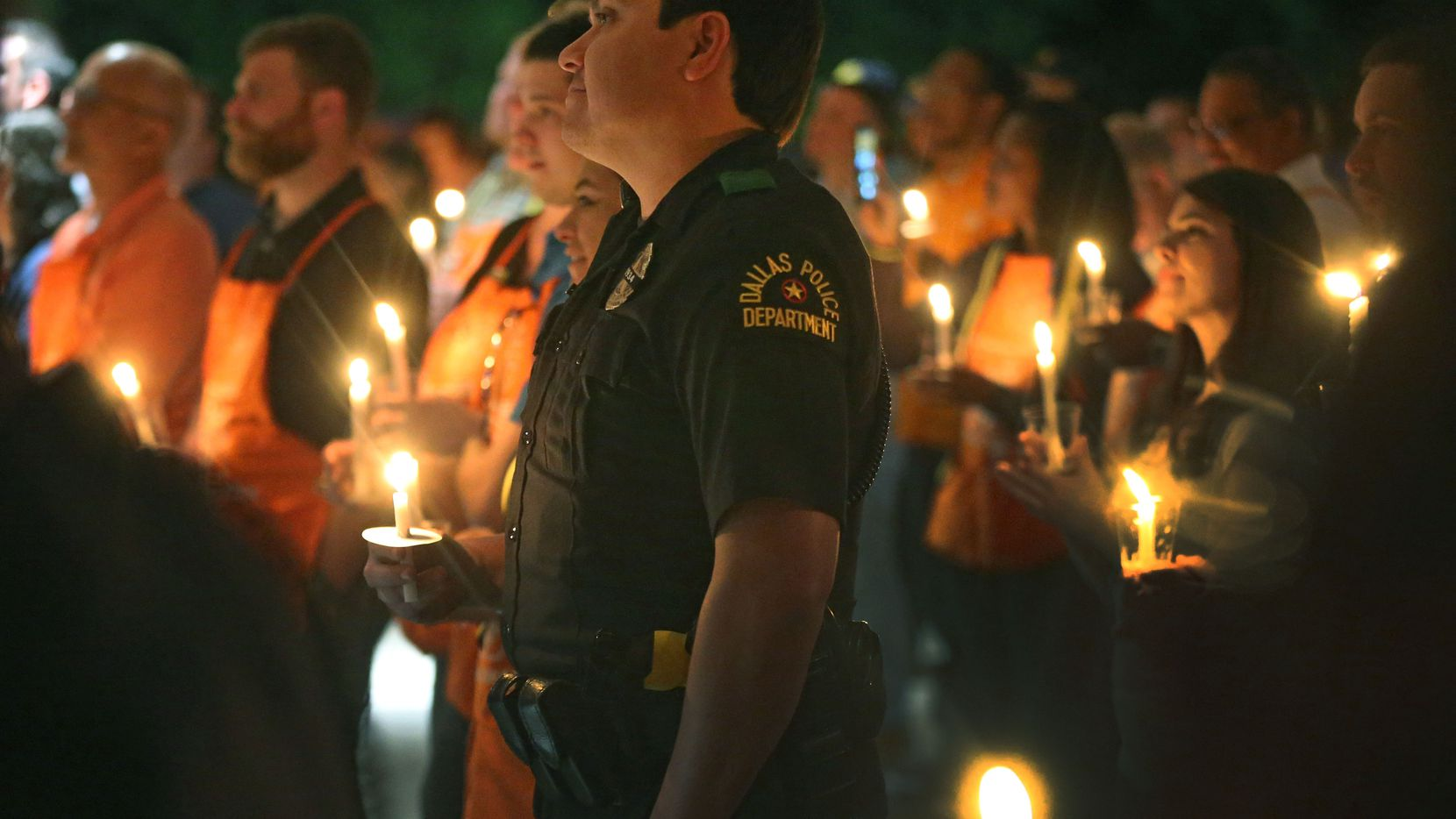A Dallas policeman stands among Home Depot employees during a candlelight vigil to support Dallas Police Officer Crystal Almeida, and to honor the memory of Officer Rogelio Santander, Jr., held at the Dallas Police Northeast Division substation on Thursday, April 26, 2018.  (Louis DeLuca/The Dallas Morning News)