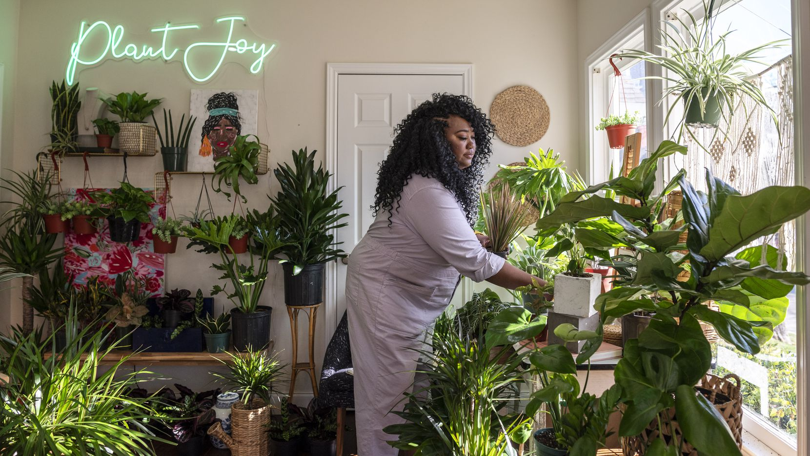 Bree Clarke, founder of The Plant Project in Uptown Dallas, organizes a couple of pots in the main display room of her shop. The Plant Project is the first plant shop in Dallas to be owned by a Black woman.