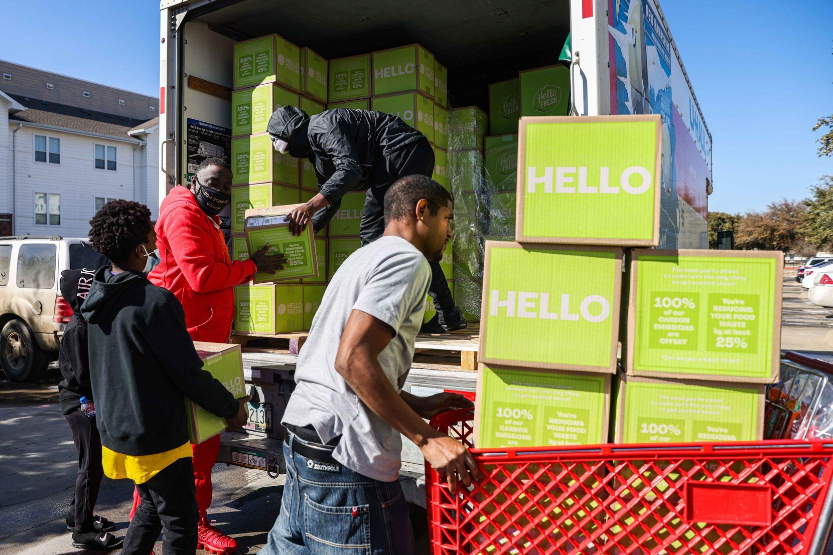 Volunteers haul boxes of food into Lakewest Senior Housing near Singleton Boulevard and Hampton Road in West Dallas on Saturday, Feb. 20, 2021.