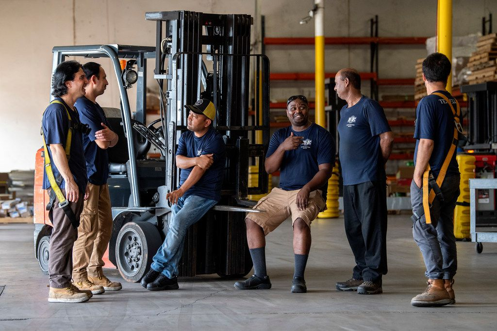 Elliott Electric Supply refugee employees Asif Ali, Muzamil Mehdi, Hussain Aklaqi, Emmanuel Habumremyi, Shafqat Masih and Abdul Fazal, left to right, chat after posing for a portrait in the regional distribution center where they work Wednesday, July 3, 2019 in Farmers Branch, Texas.