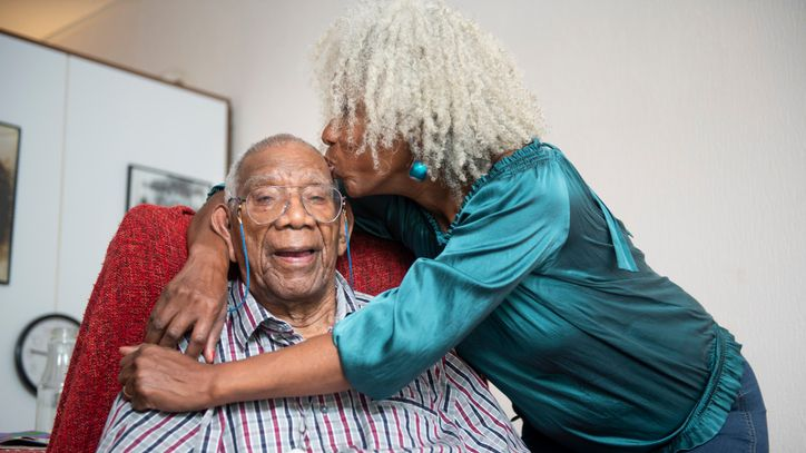 A senior woman gives her 91-year old father a kiss on the head.