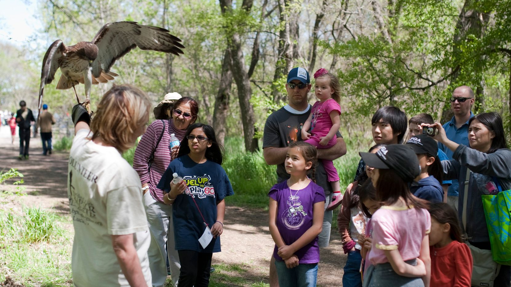 Visitors gather around Kathy Copus of the Blackland Prairie Raptor Center and her red-tailed hawk during EarthFest 2013 in this file photo at the Connemara Meadow Preserve in Allen.
