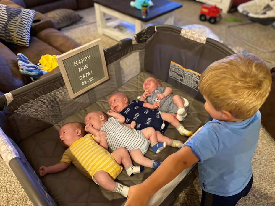 Katie and Chris Sturm's 3-year-old son, Ryan, looks over the quadruplets.
