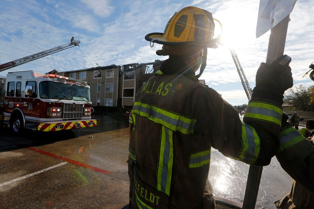 Fire crews work at the scene of an apartment fire at the intersection of I-635 and Ferguson Road in Dallas on Nov. 21, 2018.