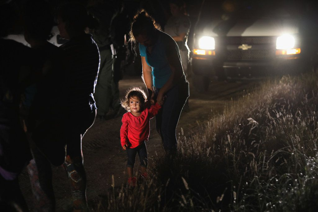 A 2-year-old Honduran stands with her mother after being detained by U.S. Border Patrol agents near the U.S.-Mexico border in McAllen.