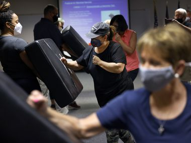 PSA flight attendant Lynyatta James (left) and Ameristar Jet Charter flight attendant Lucy Waldenstrom (center) worked on their self-defense moves with federal air marshals during a training session Tuesday at the TSA offices in Coppell.