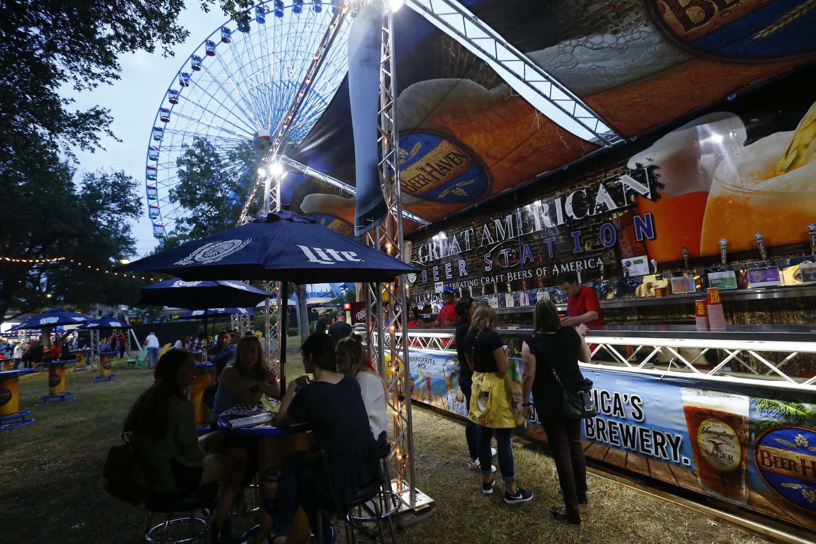 People order beers at the Beer Haven under the Ferris wheel during the State Fair of Texas in Dallas in 2017. The 2021 State Fair will be held Sept. 24 through Oct. 17.