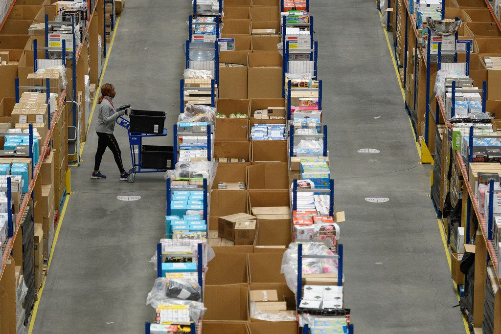 A member of staff picks customer orders from the storage shelves at an Amazon fulfillment center.