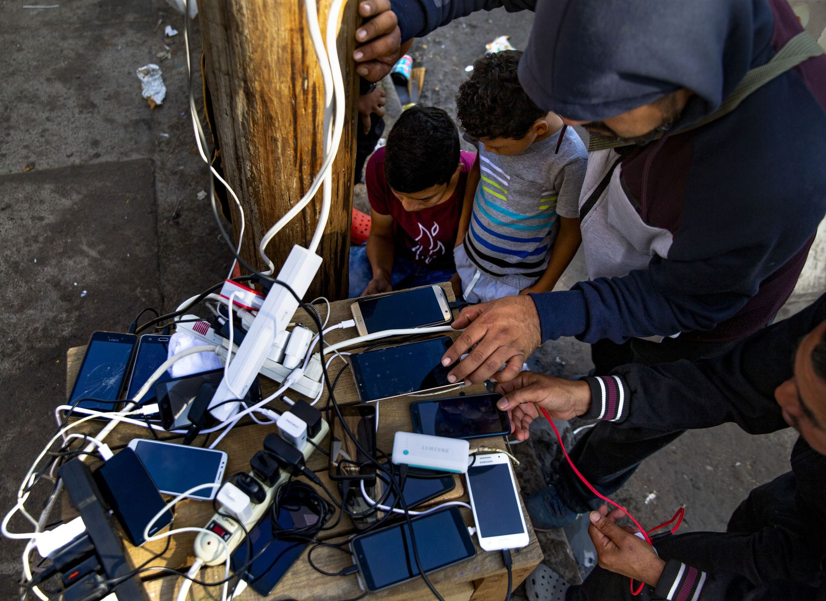 Asylum-seekers charge phones at the charging station at the temporary tent camps in Matamoros, Mexico, on Dec. 15, 2019. Residents rely on a single outlet hanging from a utility pole to charge their phones to remain in contact with relatives and lawyers.