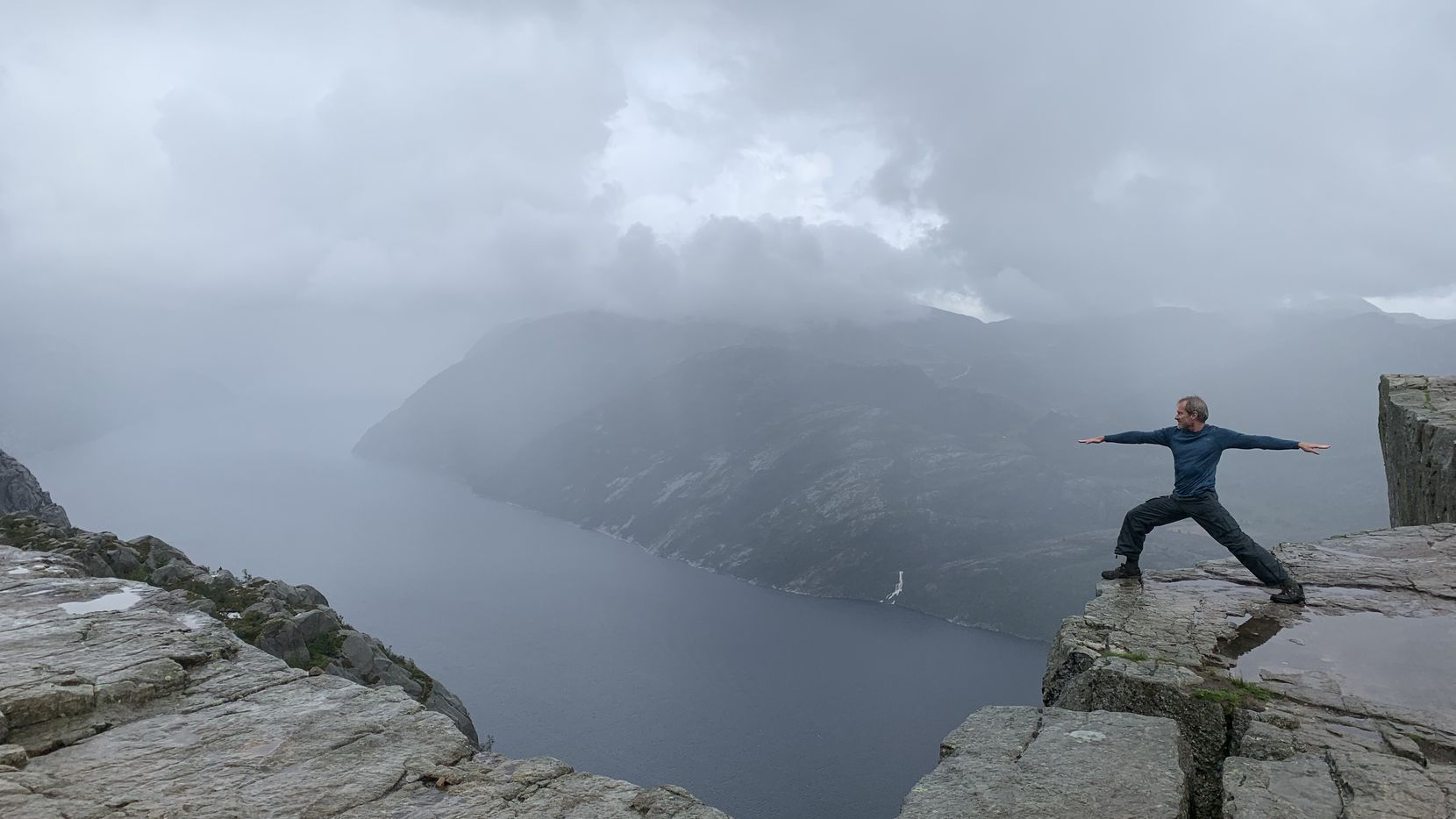 Dallas native Don Wilks practices a yoga warrior pose on the Preikestolen cliff in Norway. He's led the nomad life for 20 years.