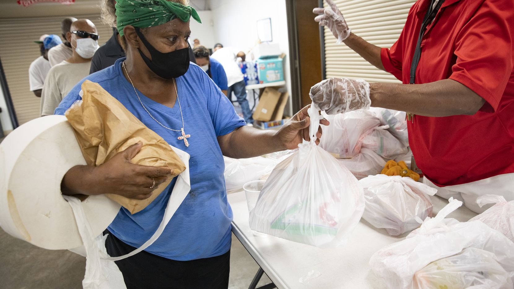 Tammy Ardmon (left) received a meal at Cornerstone Community Development Corp. in Dallas on Saturday.