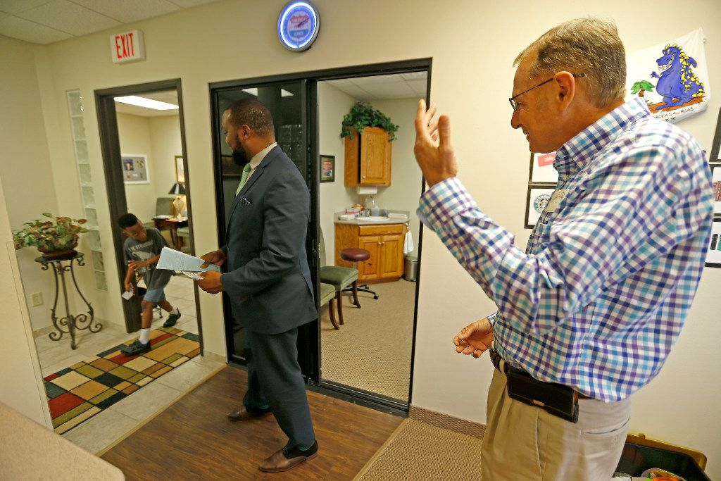 Dr. Jerome Schechter (right) and Attorney Lee Merritt (center) watch Stacy Merritt, Jr., 7, make a funny face at the North Texas Orthodontic Associates' office in Allen.