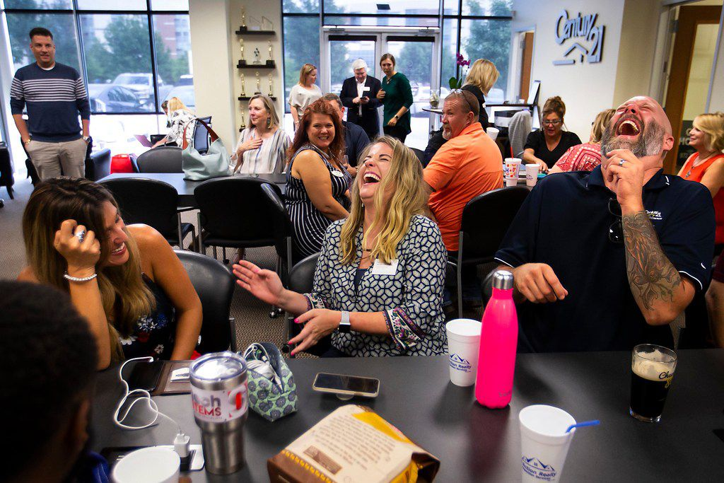 LeAnne Burnett (center) laughs with Michael Padgett and Michele Creech during a  happy hour at Century 21 Judge Fite in Mansfield.