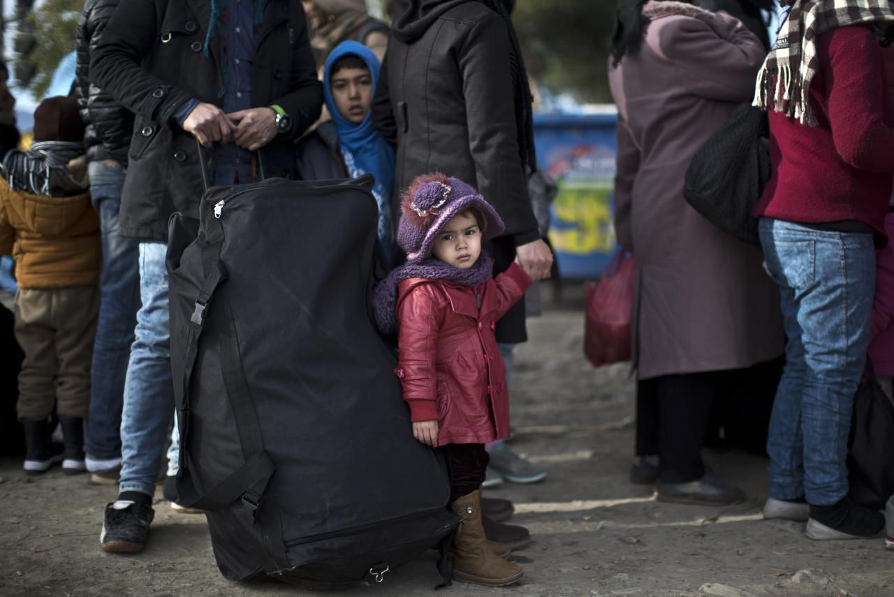 Una familia de refugiados sirios espera para cruzar la frontera entre Macedonia y Grecia. (AP/MUHAMMED MUHEISEN)