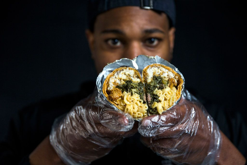"Jessie Washington, Brunchaholics owner and chef, poses for a portrait while holding a ""Soul Food Burrito"" in front of his company's booth at the Dallas Farmers Market in Dallas on Saturday, March 30, 2019. Washington said he opens at 9 a.m. Saturdays, and 10 a.m Sundays and closes at 5 p.m., unless he sells out first. (Daniel Carde/The Dallas Morning News)"