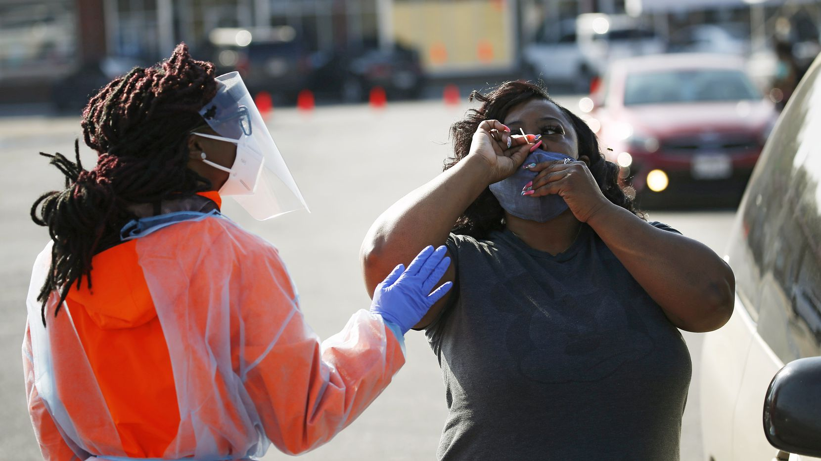 Lashara Allen (left), medical assistant helps as Charla Chappell of Dallas self-administers a COVID-19 swab test at Project Unity's free testing site at Glendale Shopping Center on Friday, November 13, 2020 in Dallas. The group is setting up daily testing sites at different locations daily.