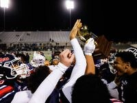 Denton Ryan football players celebrate winning the District 5-5A Division I title against Frisco Lone Star at the C.H. Collins Complex in Denton on Thursday, Dec. 4, 2020. Denton Ryan won, 35-21.