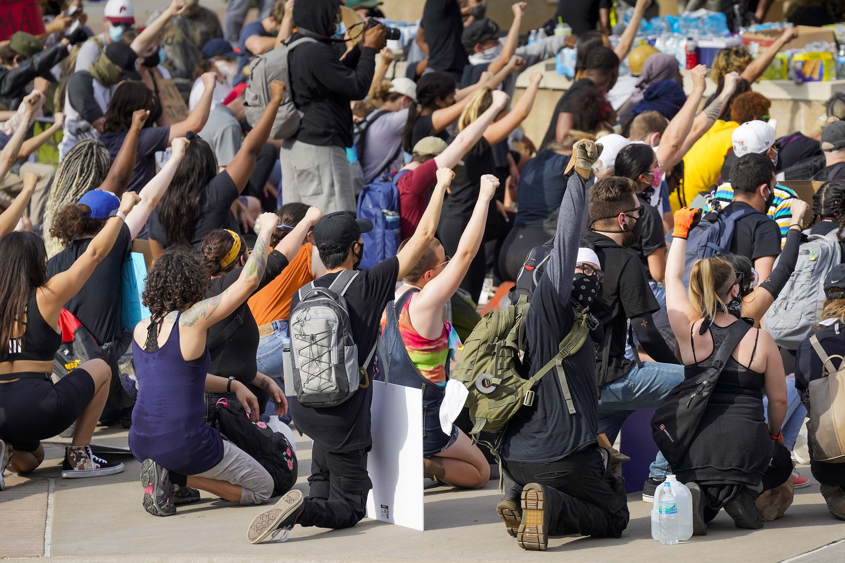 Demonstrators take a knee at Dallas Police Headquarters as protests continue after the death of George Floyd on Monday, June 1, 2020, in Dallas. Protest organizers moved the rally from the Dallas Police Headquarters to the Frank Crowley Courts Building place themselves outside of a city enforce curfew zone.