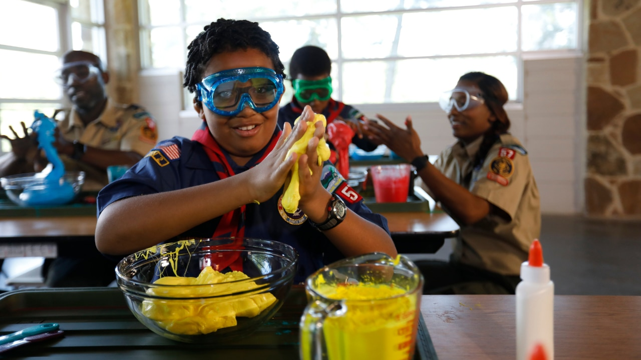 A group of young scouts participate in a science activity together.