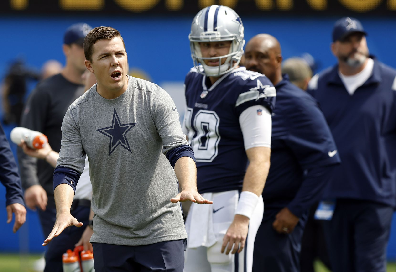 Dallas Cowboys offensive coordinator Kellen Moore motion to his players during pregame warmups before their game against the Los Angeles Chargers at SoFi Stadium in Inglewood, California, Sunday, September 19, 2021. (Tom Fox/The Dallas Morning News)