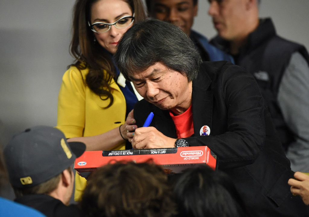 Japanese video game designer and producer Shigeru Miyamoto signs autographs during an appearance at the Apple SoHo store in New York to promote Super Mario Run for iOS. (Evan Agostini/Invision/AP)