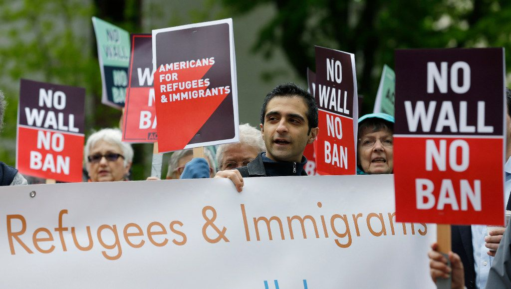 Protesters hold signs during a demonstration against President Donald Trump's revised travel ban, Monday, May 15, 2017, outside a federal courthouse in Seattle. A three-judge panel of the 9th U.S. Circuit Court of Appeals on Monday upheld a decision to block the revised travel ban, which would suspend the nation's refugee program and temporarily bar new visas for citizens of Iran, Libya, Somalia, Sudan, Syria and Yemen.