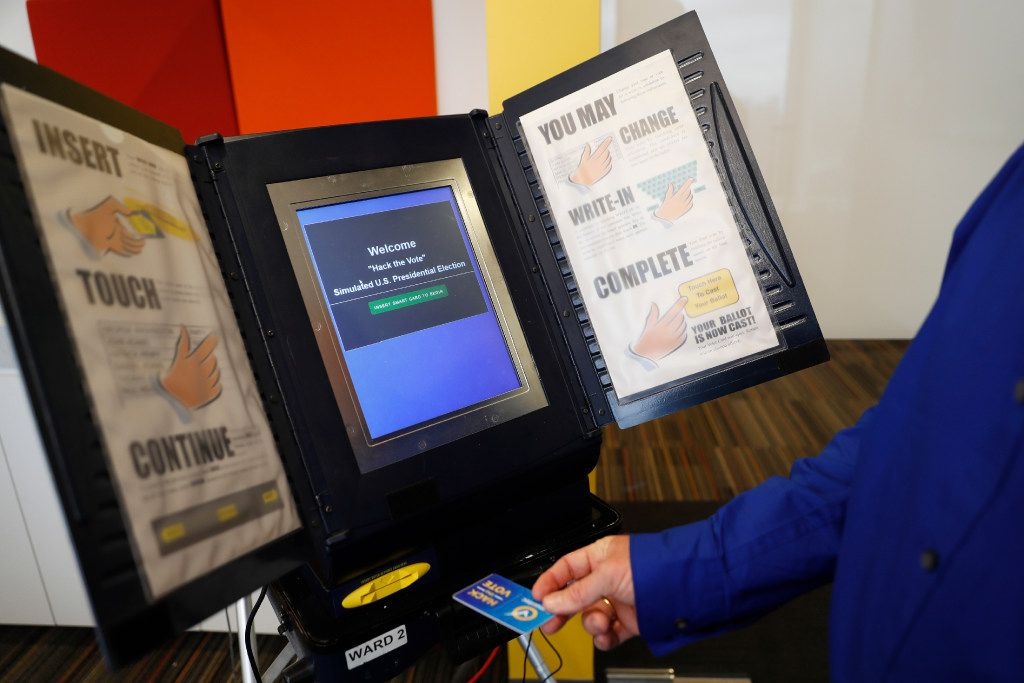 In this Wednesday, Sept. 28, 2016 file photo, Brian Varner, a principal researcher at Symantec, inserts an identifying chip card into an electronic voting machine. (Mary Altaffer/AP)