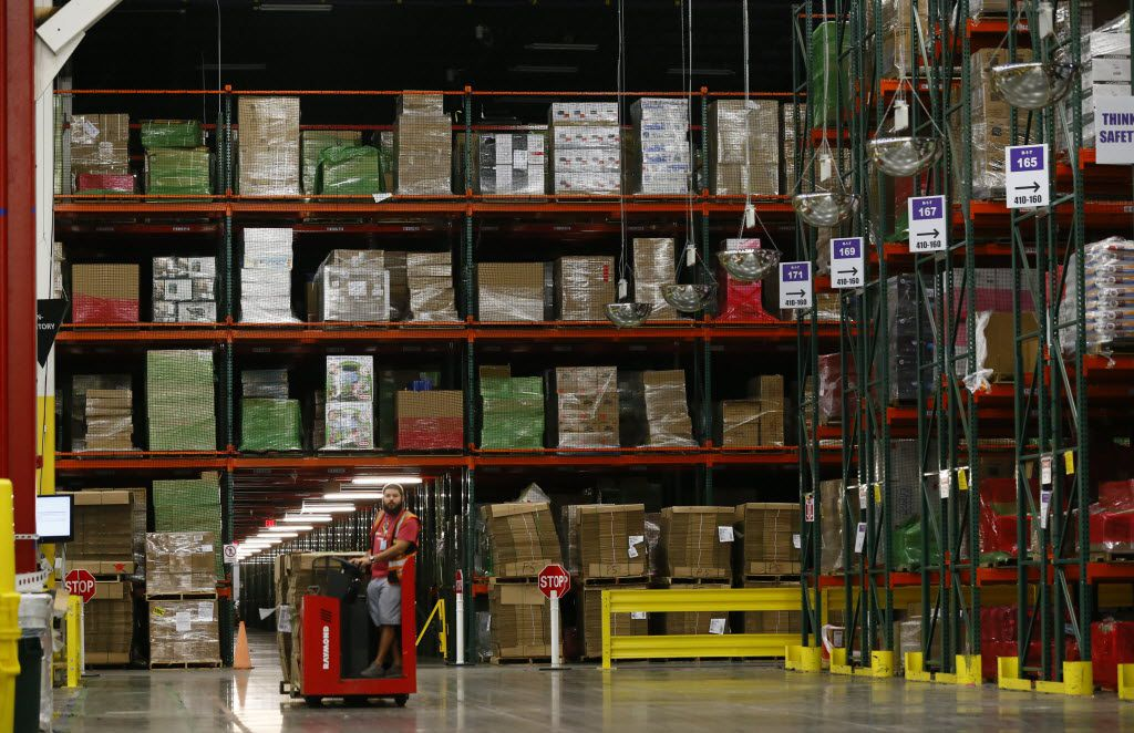 Christopher Martinez drives a pallet truck around the tons of products at Amazon's Coppell fulfillment center in 2015.