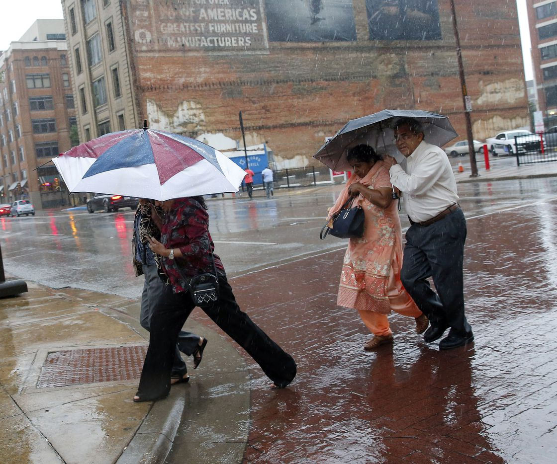 Pedestrians take cover from a heavy downpour as they cross Elm St. in downtown Dallas, Friday, June 2, 2017. (Tom Fox/The Dallas Morning News)