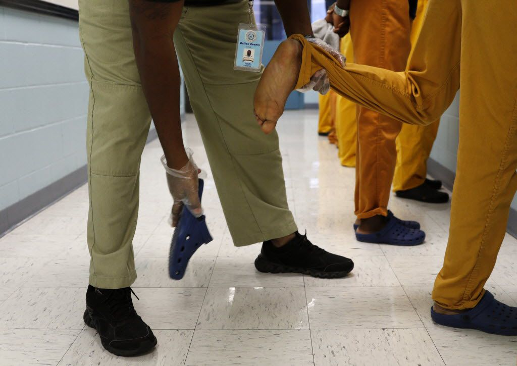 Frederick Faulk, juvenile supervision officer, takes off the shoe of an inmate during a routine search following breakfast at the Henry Wade Juvenile Justice Center in Dallas on Feb. 18. 2015. The Texas Legislature is considering major changes to how young offenders are handled, including moving 17-year-olds out of the adult criminal justice system and into the juvenile system, and considering raising the minimum age for incarceration from 10 to 13. (Rose Baca/The Dallas Morning News)