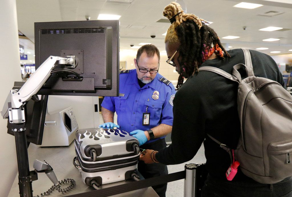 TSA officer Manuel Aguayo, left, waits as Rashad Lavaughn unlocks his bag after going through the new automated lane at Dallas/Fort Worth International Airport on Thursday, October 12, 2017.