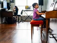 "Kamila Cabrera, 4, plays the piano as her sister Selena Cabrera, 9, does school work on a computer at the familyÕs home in Grand Prairie on Wednesday, March 18, 2020. The Cabrera family, like many around North Texas, suddenly has four youngsters at home with mom acting as ""principal"" making sure they all complete assignments as their school turns to distance learning in response to the new coronavirus. (Smiley N. Pool/The Dallas Morning News)"